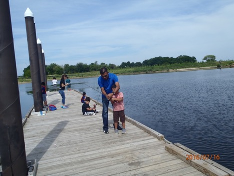 "Families fishing at Masonville Cove at the ""Conservando la Naturaleza"" Event"